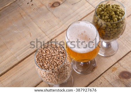 Glasses full of malt and hops over a wooden background