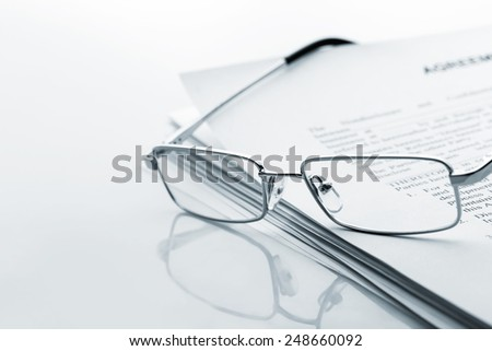 Glasses lies on the newspaper - stock photo