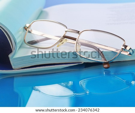 Glasses lying on a book. - stock photo