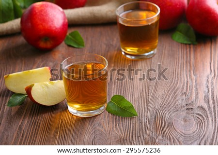Glasses of apple juice and fruits on table close up - stock photo