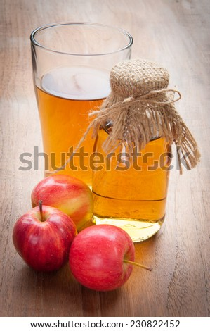 Glasses of apple juice with apples on the background. - stock photo