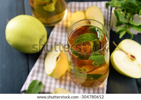 Glasses of apple juice with fruits and fresh mint on table close up - stock photo