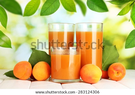 Glasses of apricot juice and fresh apricots on table on green background