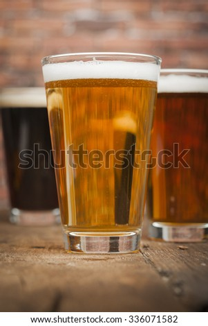 Glasses of beer on a wooden background - stock photo
