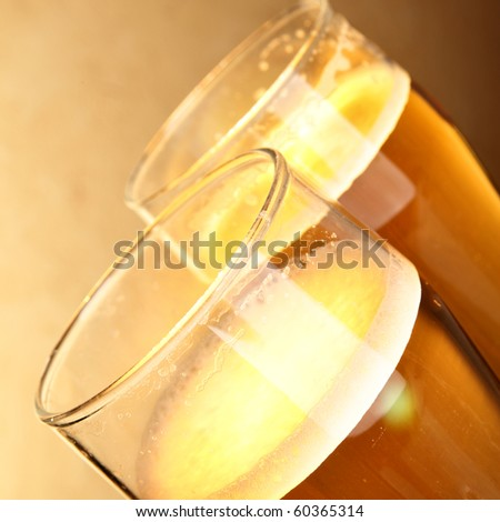 Glasses of beer with froth close-up over yellow background - stock photo
