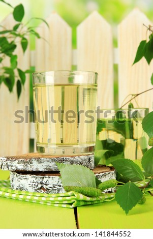 Glasses of birch sap on green wooden table