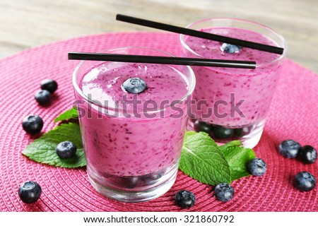 Glasses of blueberry smoothie on pink mat, closeup - stock photo