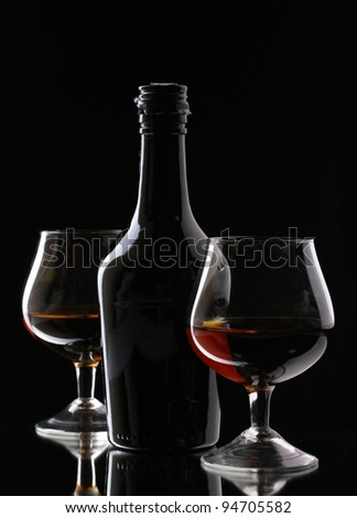 Glasses of brandy and bottle on black background - stock photo