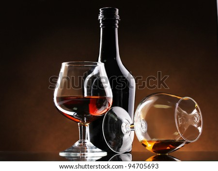 Glasses of brandy and bottle on brown background - stock photo