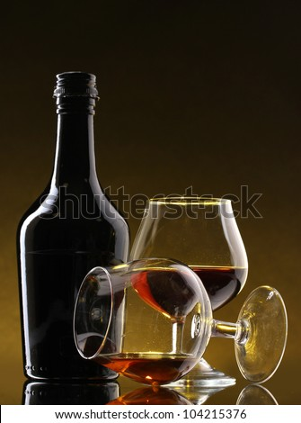 Glasses of brandy and bottle on yellow background