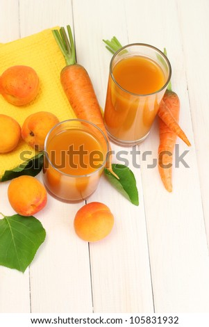 glasses of carrot and  apricot juice on white wooden table