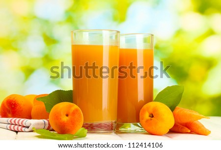 glasses of carrot and  apricot juice on white wooden table on green background