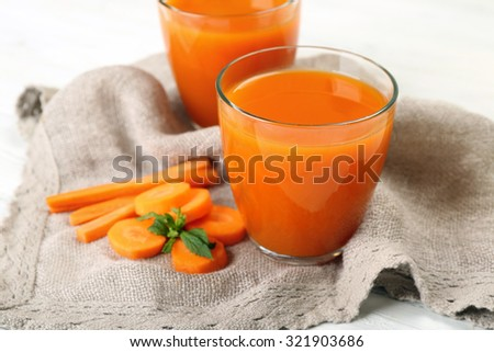 Glasses of carrot juice with vegetable slices on table close up - stock photo