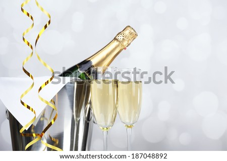 Glasses of champagne and bottle in pail on light background