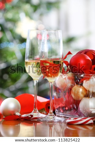 Glasses of champagne and Christmas decorations in front of Christmas tree for the holidays - stock photo