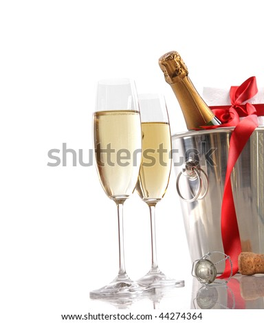 Glasses of champagne and ice bucket with red ribbon gift - stock photo