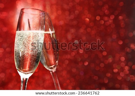 glasses of champagne and red decoration of lights  - stock photo