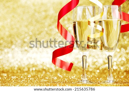 Glasses of champagne and red ribbons on golden background - stock photo
