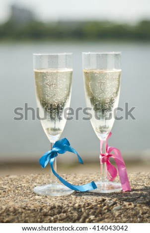 glasses of champagne and two ribbons: pink and blue - stock photo