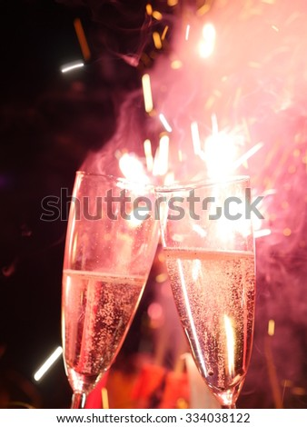 Glasses of champagne at firework on new years eve - stock photo