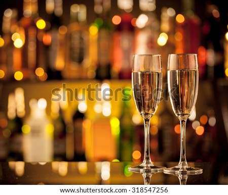 Glasses of champagne in holiday setting, served on bar counter - stock photo