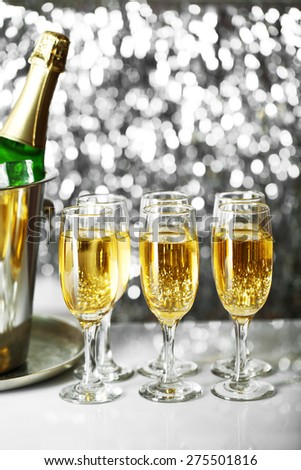 Glasses of champagne on bright background - stock photo