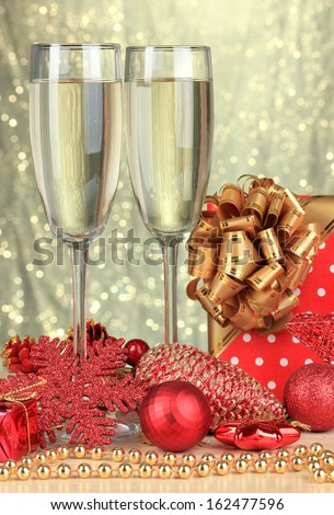 Glasses of champagne with gift box on shiny background - stock photo
