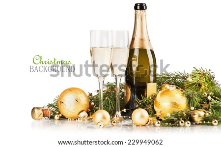 Glasses of champagne with gifts and balls on white background. Christmas background - stock photo