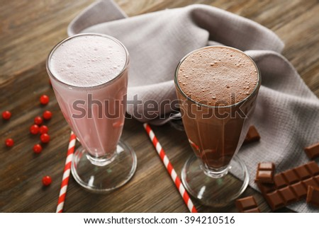 Glasses of chocolate and fruit milkshakes on wooden table closeup - stock photo