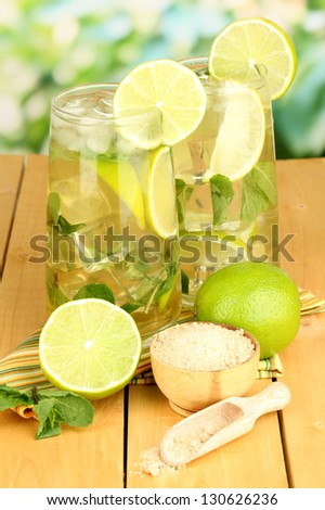 Glasses of cocktail with lime and mint on wooden table on bright background - stock photo