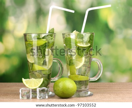 Glasses of cocktail with lime and mint on wooden table on green background - stock photo