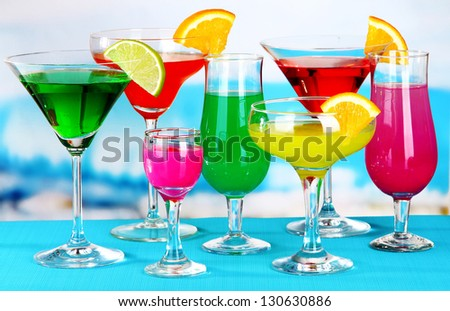 Glasses of cocktails on table near pool - stock photo