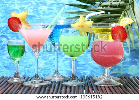 Glasses of cocktails on table on blue sea background