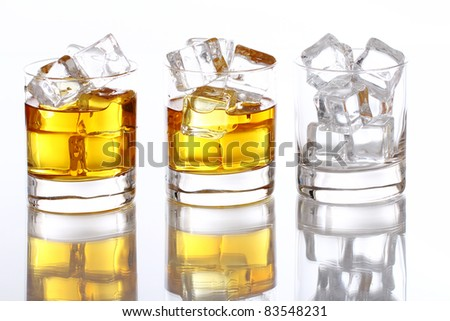 Glasses of cold whiskey with ice isolated over white - stock photo