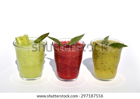 Glasses of cucumber, kiwi and raspberry smoothies with fruits and vegetables on top - stock photo