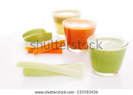 glasses of fresh vegetable juices over white background