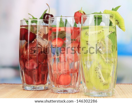 Glasses of fruit drinks with ice cubes on table in cafe - stock photo