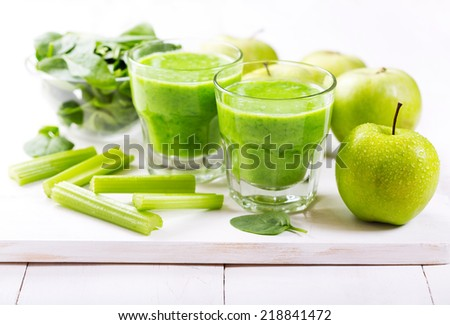 glasses of green juice with apple and spinach on wooden table - stock photo