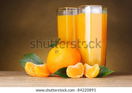 Glasses of healthy fresh juice of mandarins on brown background - stock photo