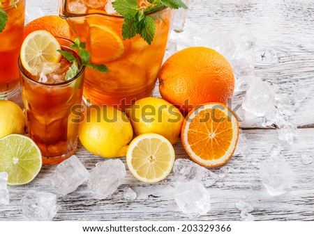 Glasses of ice tea with ice-cubes on wooden table  - stock photo