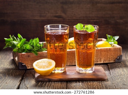 glasses of ice tea with mint and lemon on wooden table - stock photo