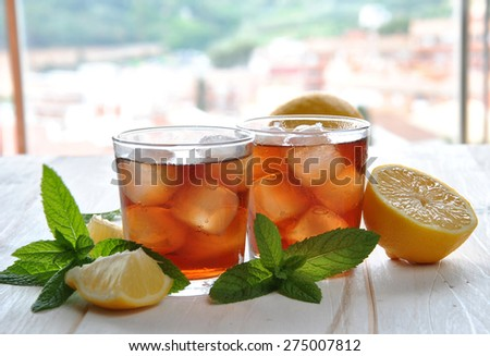 glasses of ice tea with mint leaf on wooden table - stock photo