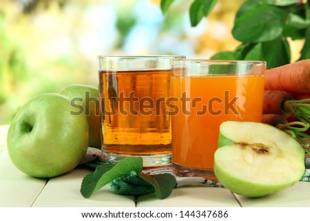 Glasses of juice, apples and carrots on white wooden table, on green background - stock photo