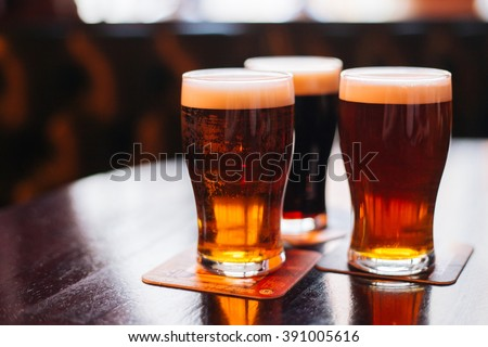 Glasses of light and dark beer on a pub background. - stock photo