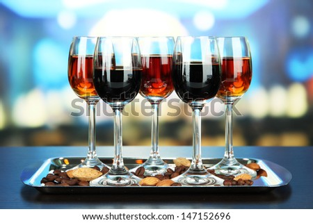 Glasses of liquors with almonds and coffee grains, on tray, on bright background - stock photo