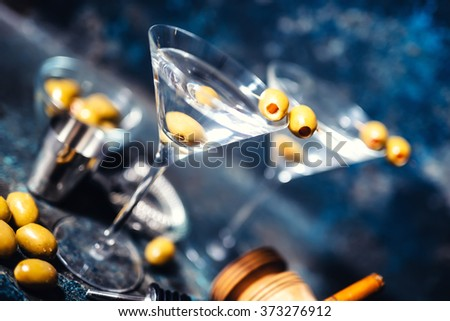 Glasses of martini with olives and vodka. Alcoholic beverages served at bar - stock photo