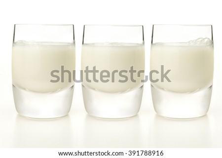 Glasses of milk on white background - stock photo