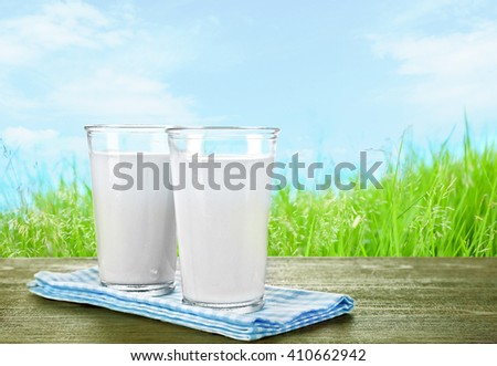 Glasses of milk on wooden table against grass and blue sky background - stock photo