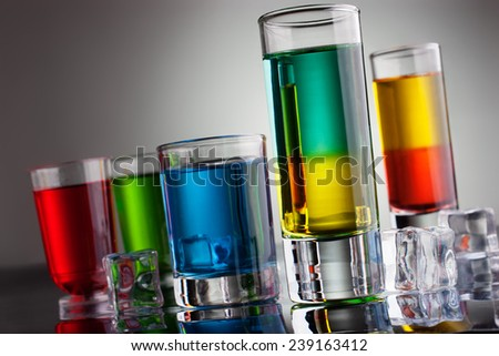 Glasses of multicoloured alcohol drinks with reflection - stock photo