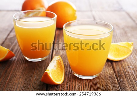 Glasses of orange juice with oranges on wooden table close up - stock photo
